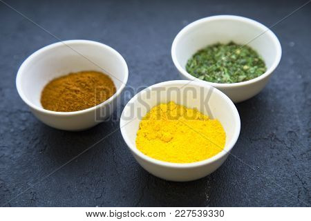 Dry Spices And Herbs In Ceramic Cups, Black Stone Background With Copy Space, Close Up