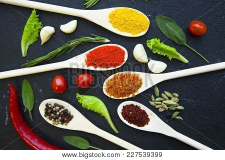 Dry Spices And Herbs In Wooden Spoons, Fresh Herbs, Cherry Tomatoes, Garlic And Chili Pepper, Black