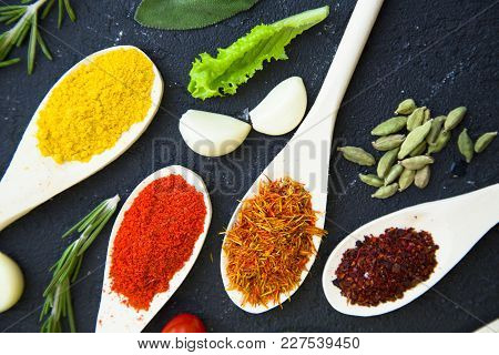 Dry Spices And Herbs In Wooden Spoons, Fresh Herbs And Garlic, Black Stone Background With Copy Spac