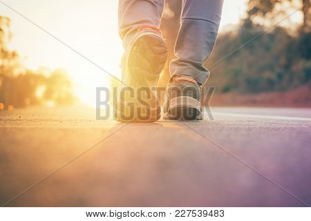 Man Walking On Road With Sun Light Flare , Close Up On Shoe Jogging Workout Wellness After Work Hard