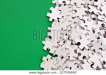 A Pile Of Uncombed Elements Of A White Jigsaw Puzzle Lies On The Background Of A Green Surface. Text