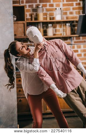 Young Woman Strangling Layman Doll In Casual Clothing At Home, Unrequited Love Concept