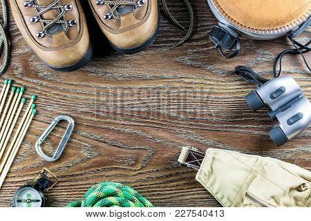 Hiking Or Travel Equipment With Boots, Compass, Binoculars, Matches And Travel Bag On Wooden Backgro