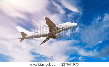 Airplane flying in the sky - travel background with flying airplane. Airplane with blank livery in the colorful sky, airplane in the flight. White commercial airplane. Sky landscape with flying airplane
