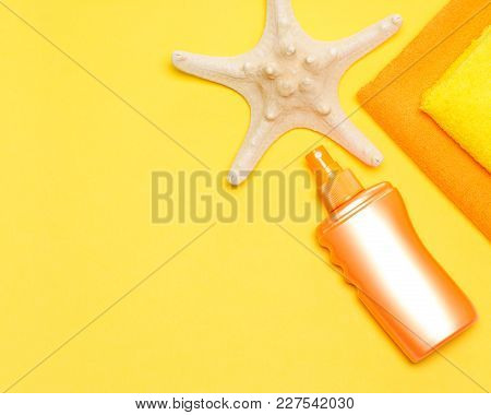 Bottle Of Sunscreen Spray With Starfish And Towels. Suntan Lotion. Copy Space