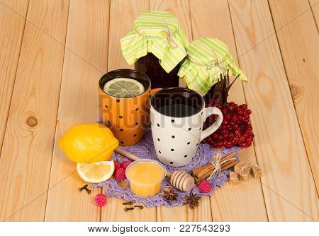 Jars With Jam, Cup Of Tea With Lemon, Honey And Spices On Wooden Surface