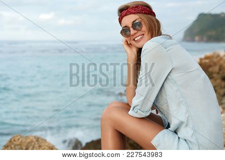Adorable Female Tourist Wears Sunglasses And Shirt, Spends Free Time Near Sea Or Ocean, Sits At Rock