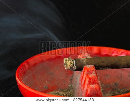 Cigar Burning In A Dirty Ash Tray Horizontal 1