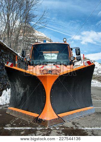 A Small Orange Truck Using Snow Plow