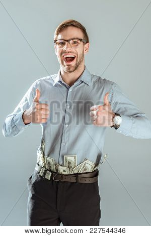 Young Excited Businessman With Dollar Bills N Pant Showing Thumbs Up Isolated On Grey