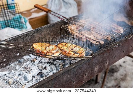 Appetizing Pieces Of Grilled Fish And Meat Cooked On The Grill Over The Hot Coals