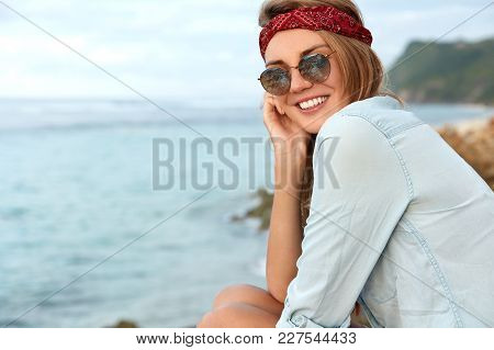 Beautiful Female Tourists Sits High On Cliff, Looks At Beautiful Ocean Or Sea View, Has Satisfied Ex