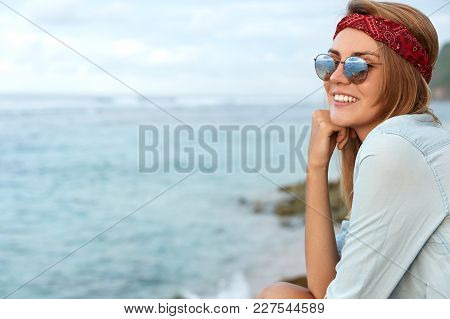 Glad Young Cute Female Hiker Wears Sunglasses And Headband, Sits On Cliff, Looks At Beautiful View O