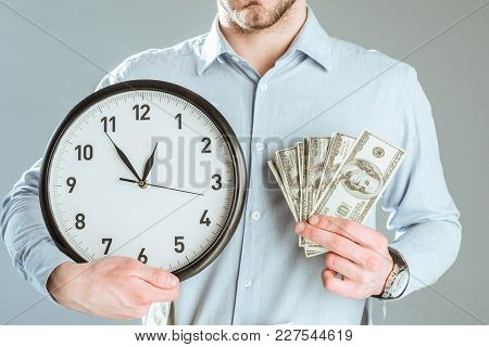 Close-up View Of Businessman Showing Money And Clock Isolated On Grey