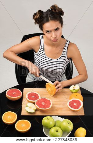 The decision to engage in a healthy diet. Young attractive woman with a sharp scowl cuts fruit poster