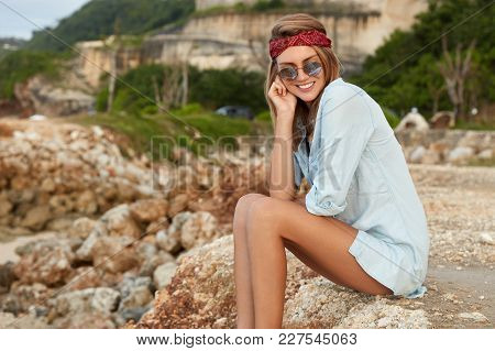 Beautiful Woman Sits On Rock With Cheerful Expression, Rests Outdoor During Hiking Tour, Enjoys Wond