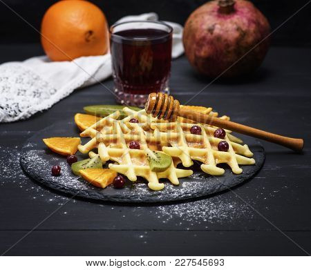 Baked Belgian Waffles And A Glass Of Pomegranate Juice On A Black Background