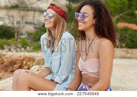 Two Mixed Raced Young Feminists Has Rest On Cliff Together, Look Happily Into Distance, Have Common