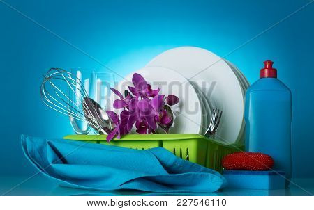 Clean Dishes On Dryer, Detergent, Sponges And Napkin, On Blue Background