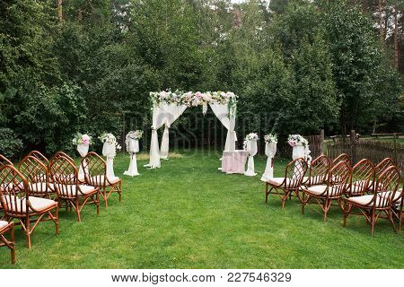 The Beautiful Platform For A Wedding Ceremony Under The Open Sky: Wooden Chairs On A Green Grass, Th