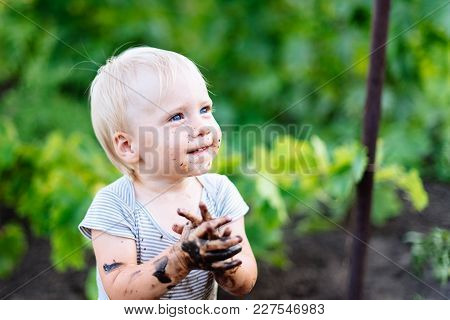 Child Playing In The Mud On The Street