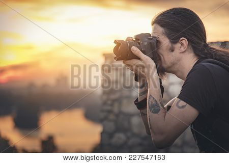 Young Photographer With Long Hair And Alternative Style Taking Photographs With His Dslr Camera, Cap