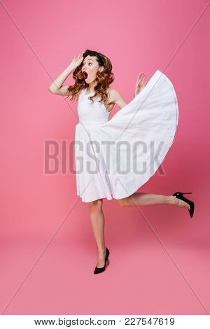 Fascinating young woman with flowing white dress taking off sunglasses and looking aside on copyspace with surprise isolated over pink background
