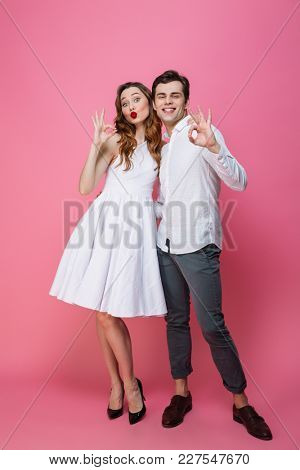 Full length portrait of an attractive smartly dressed couple showing ok gesture isolated over pink background