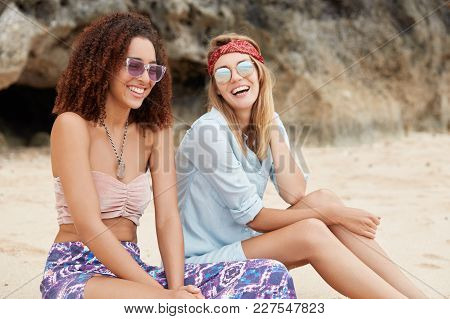 Two Happy Mixed Race Female Lesbians Sit Together At Beach, Laugh At Good Jokes, Enjoy Togetherness,