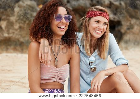 Happy Mixed Race Lesbians Sit Together On Rock, Embrace Each Other, Have Positive Expressions As Not