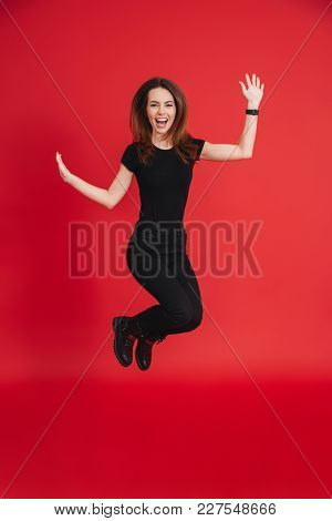 Full-length portrait of positive woman 20s wearing black t-shirt rejoicing and jumping in air isolated over red background