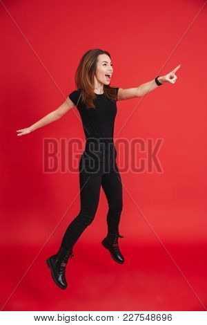 Full-length portrait of positive woman in total black outfit jumping and pointing finger aside isolated over red background