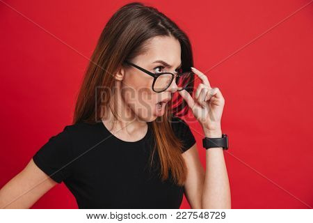Photo of young outrageous woman wearing black t-shirt taking off glasses and looking aside with indignation or shock, isolated over red background