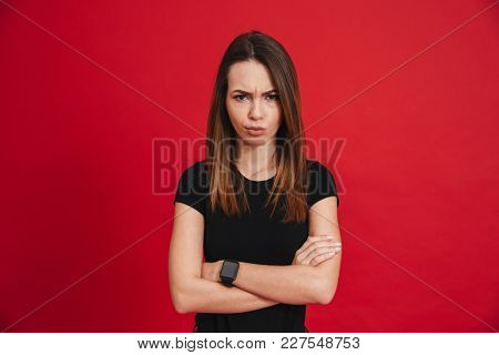 Caucasian displeased woman in black t-shirt looking on camera while frowning and posing with hands crossed isolated over red background