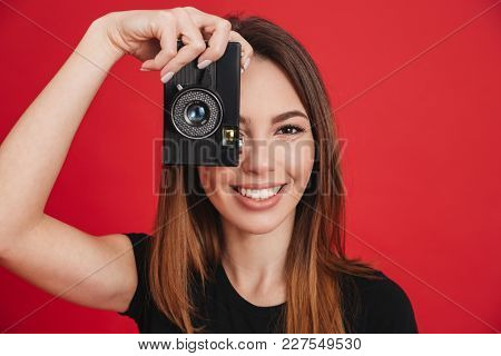 Image of joyous adult girl wearing black t-shirt holding retro camera at face and photographing isolated over red background