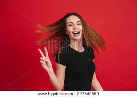 Image of positive woman with long brown hair posing on camera with showing peace sign isolated over red background