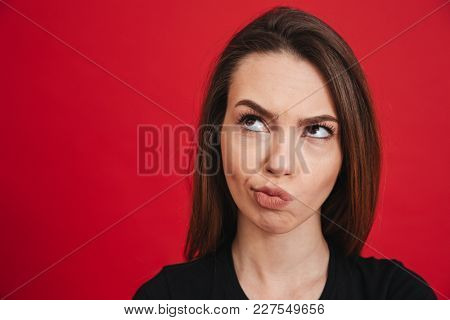 Close up photo of caucasian dissatisfied woman in black t-shirt looking upward while frowning and twisting lips, isolated over red background
