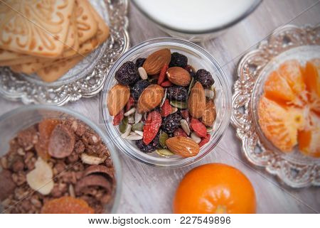 Healthy Nuts And Dried Fruits On Rustic Wooden Background. Glass Of Milk, Biscuits And Biscuits. Woo