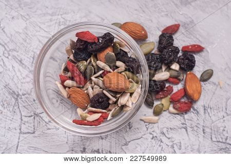 Close Up Of A Mixed Of Nuts, Dry Fruits In Glass Bowl On Gray Textured Background.