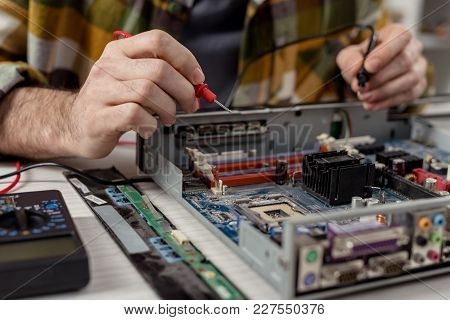 Cropped Image Of Hands With Multimeter And Broken Computer