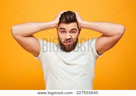 Portrait of a confused bearded man holding hands on his head isolated over yellow background