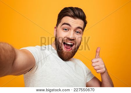 Portrait of a happy bearded man showing thumbs up gesture while taking a selfie isolated over yellow background