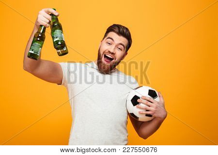 Portrait of a cheerful bearded man holding football and beer bottles isolated over yellow background