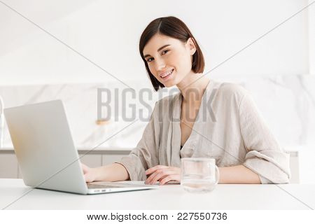 Photo of beautiful caucasian woman wearing robe looking on camera with smile while working or communicating on white notebook at home