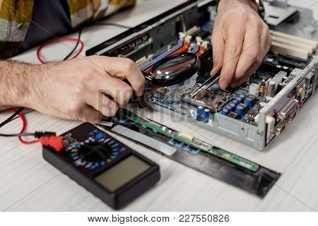 Cropped Image Of Hands Fixing Motherboard Of Pcwith Multimeter