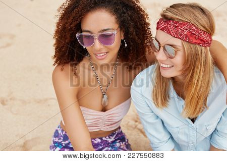 Top View Of Two Female Lesbians Embrace At Sandy Beach, Wear Sunglasses, Have Pleasant Conversation,