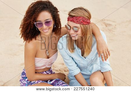 Outdoor Shot Of Female Gay Couple Spend Summer Vacations At Sandy Beach, Hug Each Other, Have Positi