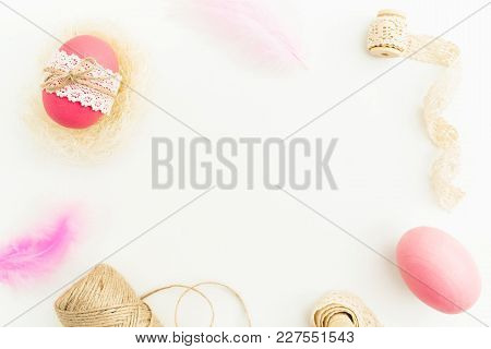 Frame Made Of Easter Pink Egg With Twine, Feathers And Tapes On White Background, Top View, Fat Lay.