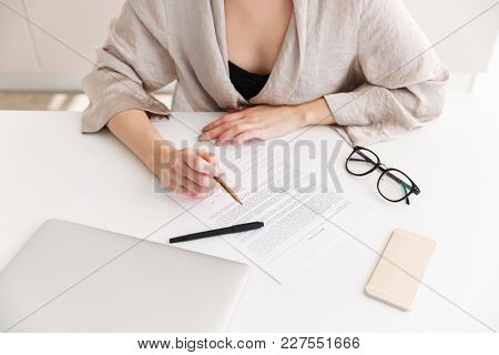 Cropped portrait of caucasian adult woman wearing robe working with documents sitting at table in home workplace