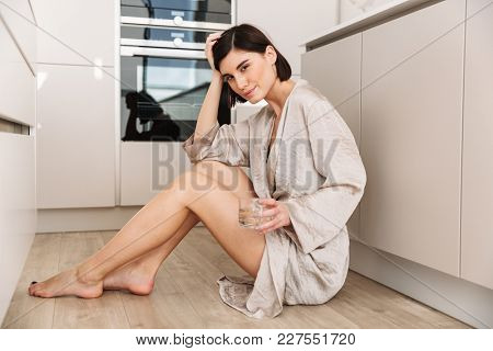 Caucasian gorgeous woman wearing robe sitting on floor in kitchen and drinking still fresh water from glass